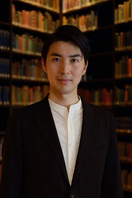 図書館のスーツを着た男性  自動的に生成された説明
